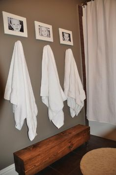 7 DIY Practical And Decorative Bathroom Ideas.  Love the bench to reach to towels and their pictures above their hooks