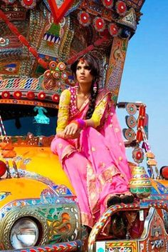 A model dressed in traditional Punjabi dress poses on a truck.
