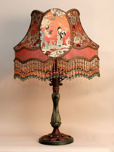 A hand-painted antique lamp base holds a hand-dyed silk lampshade covered in ornate silk Victorian ribbon and beautifully detailed Chinese silk appliques. The colours in the piece include an assortment of reds, blues, and greys as well as pale celadon green and black. Hand beaded fringe in matching tones.