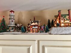 My Christmas village displayed on top of my kitchen cabinets. Christmas Tree Village, Christmas Village Collections, Christmas Yard, Christmas Villages, Christmas Kitchen, Christmas Colors, Christmas Tree Ornaments, Christmas Lights, Christmas Holidays