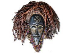 Hier geht es um eine wunderschöne Maske der Chokwe. Die traumhafte Chokwe Maske wurde aus Holz in detailverliebter Handarbeit geschaffen und mit Basthaaren, Kaurimuscheln, Perlen und Ohrringen aus Metall verziert. Die Maske der Chokwe hat eine Höhe von ca. 38cm. Zögern Sie nicht und kaufen Sie jetzt.#MaskederChokwe #ChokweMaske #Chokwe #Wandmaske #Holzmaske