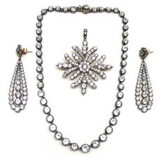 Early 19th century paste demi parure, c.1820 - comprising a riviere necklace, brooch/pendant and pair of earrings, each set throughout with white paste and close set in silver.