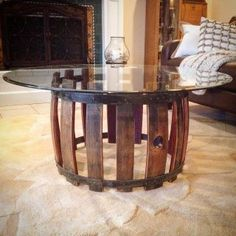 Reclaimed wine barrel coffee table featuring elements of rustic and industrial style with a modern twist. Topped with a round sheet of glass to show off the beautiful wine stained oak from their former life of aging wines.