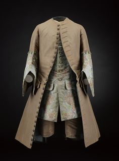 Man's coat of brown corded silk, British, c. 1735. With large cuffs made from brocaded fabric in silk and metal thread, featuring a floral pattern in shades of green, blue, pink and silver on a light blue ground. The skirts are padded with wadding and the buttons are covered with metallic thread part of a suit | National Museums Scotland
