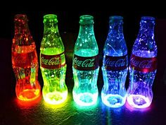 Looks like someone cracked open some glow sticks & poured them in old classic Coca Cola bottles. Cool rainbow lighting!