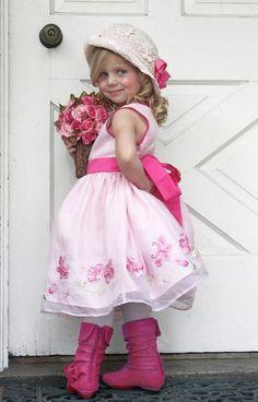 Little princess in front of a barn door