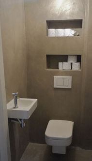 wall cut outs to hold toilet paper etc - add cabinet doors or art work on hinges over the top!