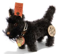 Price Realized    ($6,926) A STEIFF SALESMAN'S SAMPLE HEAD-TURNING SCOTTY, (1309,0H), standing, gray/black mohair, brown and black glass eyes, brown stitching, felt ear lining, htail operated head-turning mechanism, collar with button and card tag, FF button with red tag and white card handwritten sample tag, 1932 --4½in. (11.5cm.) long (button on collar rusty)