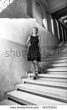 Black and white photo of elegant woman in short dress walking down marble stairs