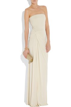Asymmetric draping elevates Gucci's classic ivory matte-jersey gown to a standout bridal piece. Accent the elegant lines with metallic strappy sandals and gold accessories. Shown here with a Jimmy Choo clutch, Alaïa heels and a Gucci bracelet, bangle and ring.