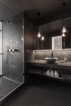 Moderne badkamer in donkere uitvoering. De glazen douchewand zorgt voor een transparante en ruimtelijke look.