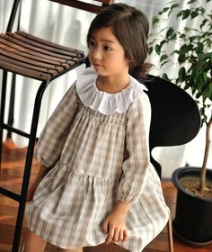 Flora Girls Checkered Dress  It doesn't get more classic than this. Beautiful creams, lots of texture, low contrast pattern and movement against the deep green of the xmas trees. So pretty!  Greenberry Kids - 29.40pounds