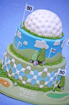 """""""A cake for an avid golfer turning 50. The golf ball is also cake and the tall flags are taper candles and paper. The sand trap is filled with graham cracker crumbs and the pool is tinted homemade piping gel. The argyle pattern is probably the most time-consuming decoration I've ever done!   Thanks to jylbug whose idea I stole (with permission) and did not do justice to!"""""""
