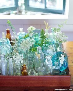 a tray full of old glass bottles to brighten a room
