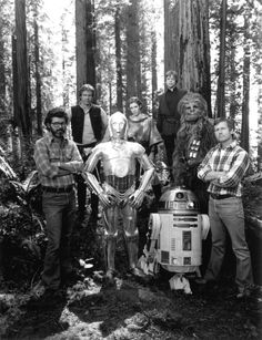 """On the set with the cast and crew of """"Star Wars: Revenge of the Jedi"""", 1982.  Front row (L to R): co-writer/executive producer George Lucas, Anthony Daniels (as C-3PO), Kenny Baker (as R2-D2), director Richard Marquand.  Back row (L to R): Harrison Ford, Carrie Fisher, Mark Hamill, Peter Mayhew (as Chewbacca).  Once again, Lucas wrote and produced the movie but didn't want to direct.  He offered the movie to David Lynch and David Cronenberg but both declined in favor of other projects…"""