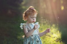 Summer photo ideas. Toddler spring picture session in the evening. Fairytale pictures of little girls or boys. Unique 2, 3, 4, 5, 6, 7, 8 year old picture session ideas. Photos of youth with sunset during golden hour blowing dandelion puff flowers. Birthday or mommy and me baby infant toddler portrait ideas. Super cute shabby chic rustic mini session shoot in forest on sun lit path with bunny rabbit picture. Woodland photos of toddler. Lauren Davidson Photography.