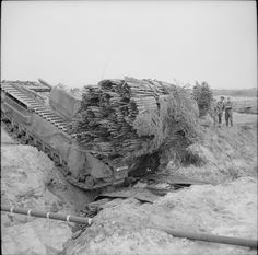AVREs were used to transport fascines - large bundles of wooden sticks and other materials used to bridge gaps in the ground. The AVRE would release the fascine into these gaps to create a passable surface. Tank-carried fascines were first used during the First World War to fill trenches that were either too wide or too deep for vehicles to cross.