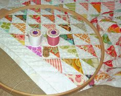 She basted a scrap piece of fabric around the outside of the quilt to give her more fabric to put in the hoop