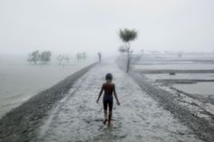 BANGLADESH. Sathkira District. 2010. During a storm squall, a girl walks a long an embankment that was broken by the 2009 cyclone Aila. The surrounding areas were still flooded a year later, with many embankments unrepaired.