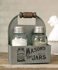 This charming Mason jar caddy measures 4 inches wide, 2 inches deep and 5 inches high. This metal caddy holds one salt and pepper shaker set with the classic Mason jar logo printed on the front. A wooden handle adds a rustic touch. Salt and pepper shakers are included.