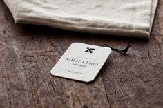 love everything about this hang tag, paper, shape, letterpress, hole & threading