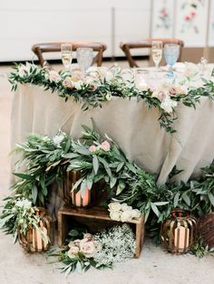 a head table decorated with green garlands, blush blooms and lanterns | Photography: Esther & Smith