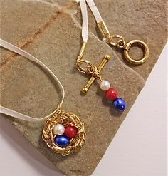 patriotic gold copper nest necklace with red coral and white and blue freshwater pear eggs, hung on thin white ribbon with pretty toggle and extra red, white, blue bead accent.