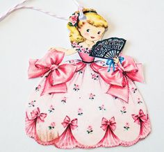 This is a set of 3 Retro Gift Tags featuring a beautiful girl in an elegant pink ball gown with bows, flowers in her hair and holding a black fan. The