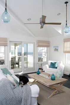 beachy shades, white slip covers, wood coffee table, white walls with blue accents