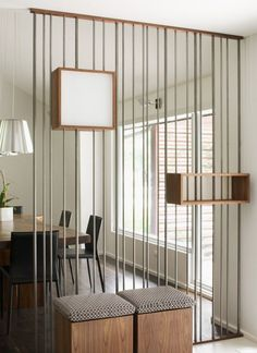 Lineal dividing wall holds simple timber shelving, a nice design