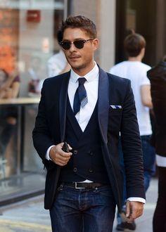 Comprar ropa de este look:  https://lookastic.es/moda-hombre/looks/blazer-chaleco-de-vestir-camisa-de-manga-larga-vaqueros-corbata-panuelo-de-bolsillo-correa-gafas-de-sol/6075  — Gafas de Sol Marrón Oscuro  — Camisa de Manga Larga Blanca  — Corbata Azul Marino  — Vaqueros Azul Marino  — Correa de Cuero Negra  — Blazer Azul Marino  — Chaleco de Vestir Azul Marino  — Pañuelo de Bolsillo de Rayas Verticales Blanco y Azul Marino