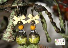 die perlenkombi ist ca 36 mm lang und 12 mm breit. es handelt sich um alte olivgrüne jadesteine, mit messingfarbenen perlenkappen versehen und gekrönt von ein wenig strassdeko sowie einer kleinen facettierten tschechischen glasperle in senfgelb.