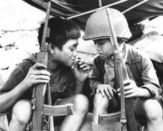 Vietnam War Weapons - Vietcong child fighters share a cigarette.. Both are holding U.S. M-2 .30 carbines
