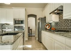 Grey/green backsplash // White cabinetry // Light granite countertops