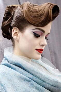 World War 2 look inspired. Exaggerated flicks and extended eyebrows with full red lip. Mave tone on the eyelids. Cool wavy set hair up.