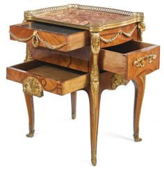A TRANSITION STYLE GILT-BRONZE MOUNTED KINGWOOD AND TULIPWOOD TABLE À ÉCRIRE FRANCE, EARLY 20TH CENTURY, AFTER THE MODEL BY JEAN-FRANÇOIS OEBEN surmounted by a brocatelle rouge du Jura, the frieze drawer opening to a writing slide, above a deep drawer opening from the proper left side and above a smaller front lower drawer height 29 in.; width 23 in.; depth 18 1/2 in. 74 cm; 58.5 cm; 47 cm