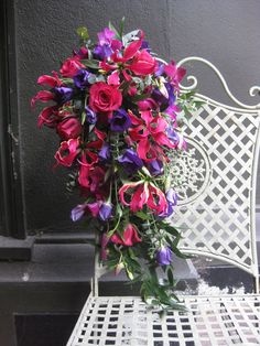 Bride's cascade bouquet of gloriosa lilies, lisianthus, roses, dendrobium orchids and ruscus
