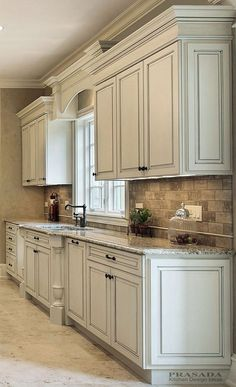 Antique White Cabinets with Clipped Corners on the Bump Out Sink, Granite Countertop, Arched Valance.