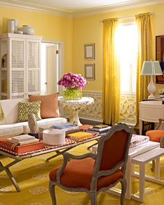 This living room features a bold palette of apricot, yellow, and white.