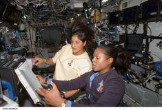 Building the Space Station Astronauts Joan Higginbotham (foreground) and Suni Williams refer to a procedures checklist as they work the controls of the Canadarm2 in this 2006 image.