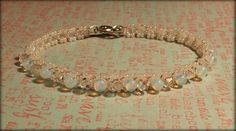 Hand woven tennis bracelet with round opal beads and swarovski ab clear crystals. Jewlry by Designs by Melody