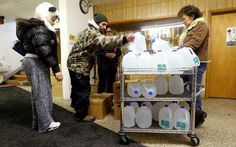 Flint residents receive free water being distributed at the Lincoln Park United Methodist Church in Flint, Mich. Feb. 3, 2015. (AP Photo/Paul Sancya)