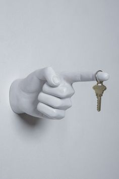 Interior Illusions One Finger Pointing Wall Hook. Shaped with a pointed finger, the One Finger Pointing Wall Hook works as a stand-alone decorative piece or as a stylish hanger for small items. The handmade piece is finished in white resin and makes a unique addition to modern decor. Attach it to an entryway wall for hanging keys or a bedroom for hanging jewelry.