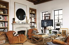R Lauren, modern art, warm brown upholstery, tv on easel, built-in bookshelves in contrasting wood - masculine, handsome apartment