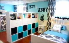 blue girls' room with black on white damask curtains, divided by a stack of ikea shelves as a makeshift wall