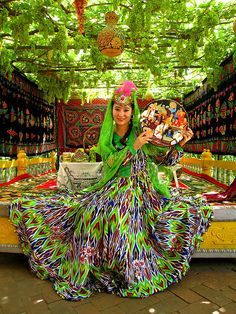 An Uyghur woman in kaleidoscopicly awesome traditional costume. Uyghurs are a Turkic ethnic group living in Eastern and Central Asia, who live primarily in the Xinjiang Uyghur Autonomous Region in the People's Republic of China. Outside of China, significant diasporic communities of Uyghurs exist in the Central Asian countries of Kazakhstan, Kyrgyzstan, and Uzbekistan.