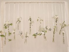 Glass milk bottles and a few stems in monochromatic shades tied securely to your arch or a ceiling beam create a wow-worthy hanging installation that makes for a pretty wedding ceremony backdrop (and an easy DIY project).