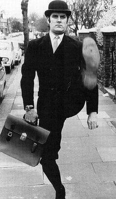 "John Cleese as the Minister for Silly Walks in MONTY PYTHON'S FLYING CIRCUS - ""Face the Press"""
