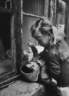 A young girl playing with a doll on the windowsill of her apartment. Photograph by Stan Wayman. Moscow, Russia, September 1963.