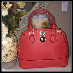 "STUDDED DOME BAG IN RAGING RED Classic dome shaped studded satchel with zipper top closure.  Textured vegan leather with rear zipper pocket. Fully lined inside with open and zippered pockets. 18"" handles to carry at wrist as satchel, or add the additional 50"" strap to carry as shoulder or crossbody style.  13Wx5.5Dx10.5H Boutique Bags Satchels"